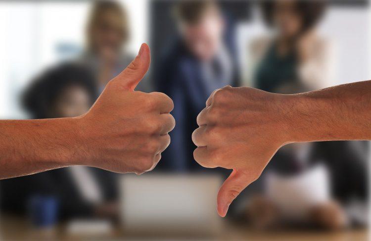 Paralelas uma a outra, uma mão faz sinal de dedão para baixo. Em contrapartida, a outra aponta o dedão para cima.